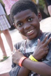 Little Boy crossing his arms with a peace sign