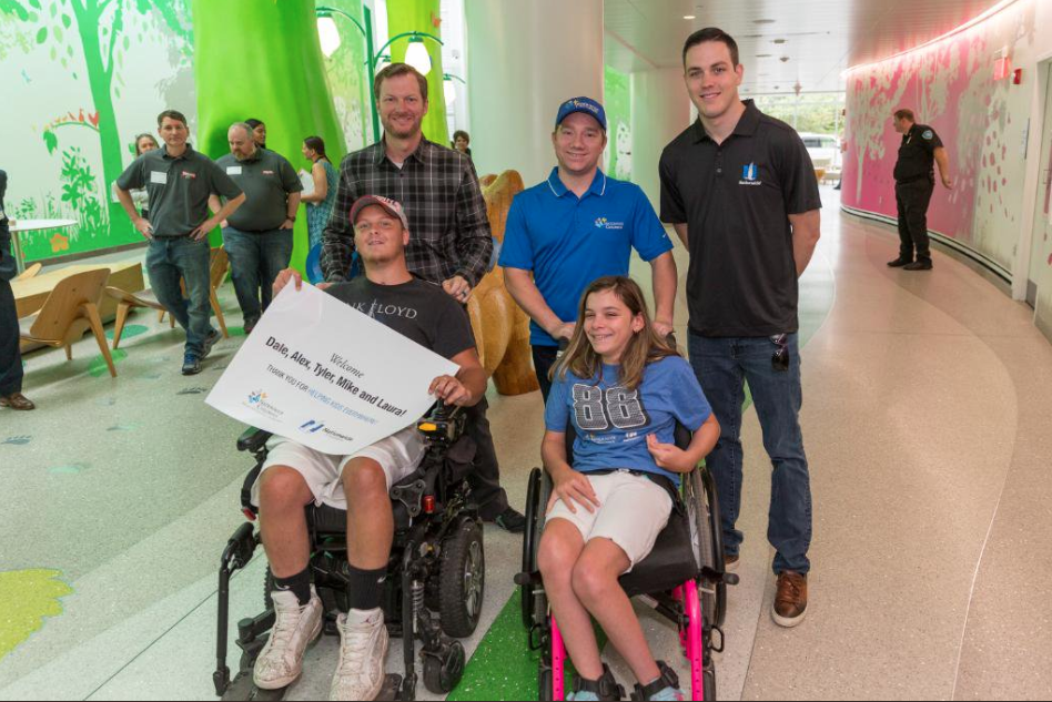 Dale Jr, Tyler Reddick and Alex Bowman pose with two patients in wheelchairs at Nationwide Children's Hospital